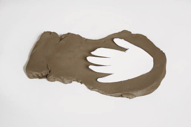 paper hand on clay